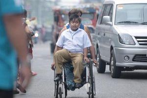 Xúc động cảnh người cha tật nguyền đưa con trai đi học bằng xe lăn