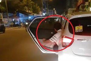 Người đàn ông mở cửa sau, thò người ra ngoài khi ôtô đang chạy