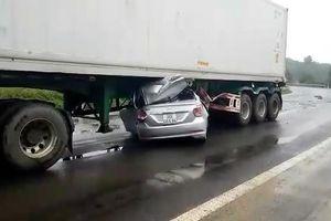 Xe ô tô nằm gọn trong gầm container sau tai nạn
