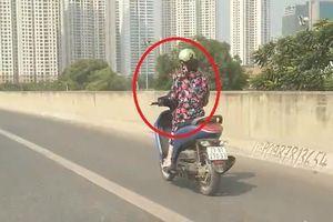 Người phụ nữ vừa lái xe máy vừa dùng điện thoại trên cao tốc