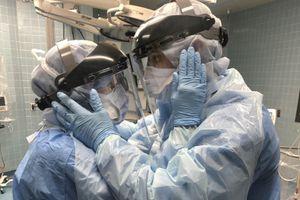 Vợ chồng y tá âu yếm nhìn nhau qua tấm kính bảo hộ trong phòng cấp cứu