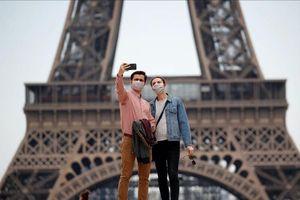 Du khách đeo khẩu trang chụp ảnh tại các điểm đến nổi tiếng thế giới