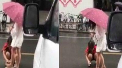 Con gái bắt mẹ ngồi xổm trên đường lau chân cho mình gây phẫn nộ