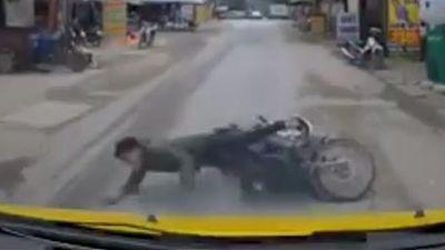 Dùng điện thoại khi chạy xe máy, thanh niên ngã trước đầu xe ôtô