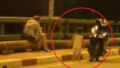 Người mẹ mải bấm điện thoại để con chơi giữa cầu đầy xe cộ