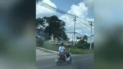 Thanh niên ngồi vắt chân, dùng một tay lái xe máy với tốc độ cao
