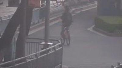 Người đàn ông Trung Quốc lái xe đạp đi lùi trên phố đông người