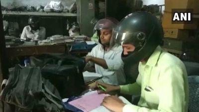 Kỳ quặc nhân viên ngồi trong nhà cũng đội mũ bảo hiểm là vì...