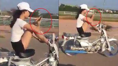 Nữ tài xế dùng chân lái xe máy, tay bấm điện thoại