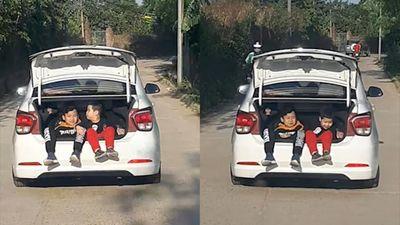Ôtô chở 2 bé trai ngồi trong cốp xe chạy trên đường