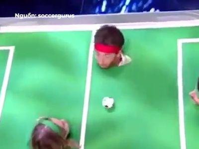 Mỗi người chơi được đưa đầu qua chiếc lỗ nhỏ trên bàn đấu, sau đó phải dùng hơi thổi thật mạnh để điều khiển quả bóng. Trông thật thú vị phải không nào?
