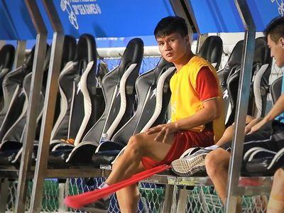 Nguyễn Quang Hải thực hiện các bài tập nhẹ ở ngay ghế ngồi khu vực kỹ thuật của U22 Việt Nam trong trận đấu với U22 Campuchia. Anh đang bị chấn thương và cần thời gian để hồi phục.