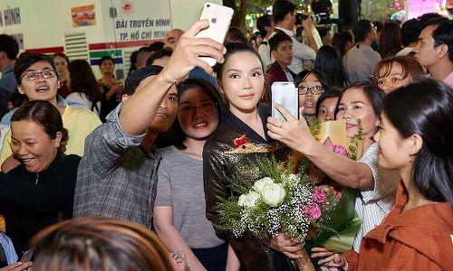 Lý Nhã Kỳ mặc áo dài dát vàng nổi bật ở phố đi bộ Nguyễn Huệ