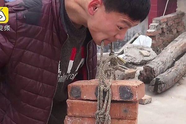Xem chàng trai dùng răng nâng hàng chục viên gạch