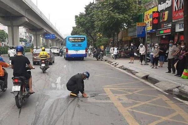 Người đàn ông dọn vết dầu thải bị đổ giữa đường