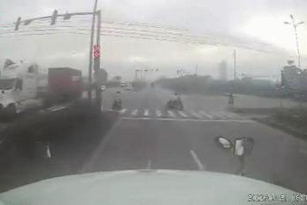 Clip: Tài xế container đánh lái tránh hai người chạy xe máy sang đường thiếu quan sát